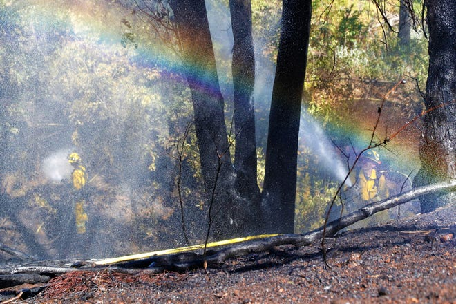 Sunlight shining through water sprayed from firefighters' hoses creates a rainbow effect during a vegetation fire near the corner of Hartnell Avenue and Alta Mesa Drive in Redding on Thursday, June 24, 2021. The fire burned about an acre of grass, brush and trees on a hillside beside a creekbed.