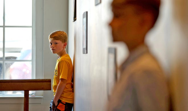 Jenson Meyers, left, stands near his artwork depicting the iconic Hank the Cowdog character on the walls of the Cooper Gallery on Wednesday, June 23, 2021.