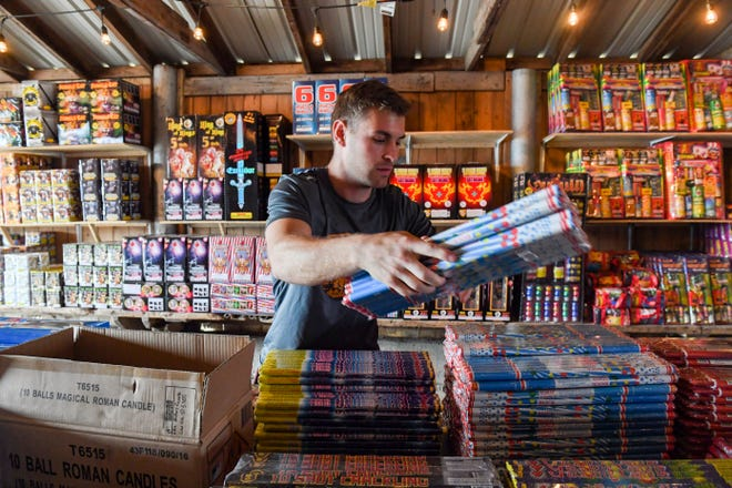 Austin Green piles bottle rockets on a table ahead of the Fourth of July on Thursday, June 24, 2021, at Fire Bros. Fireworks in Sioux Falls.