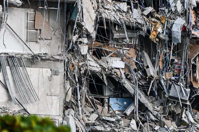 Rubble hangs from a partially collapsed building in Surfside north of Miami Beach, on June 24, 2021.
