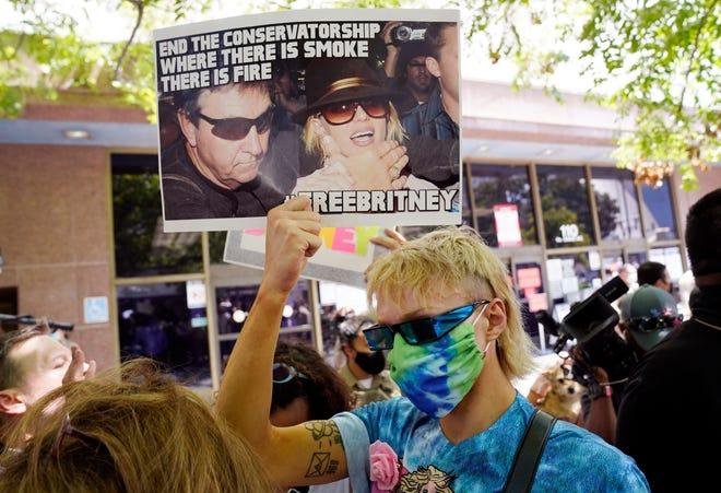 Britney Spears supporter Biblegirl holds a sign outside a court hearing regarding the pop singer's guardianship.