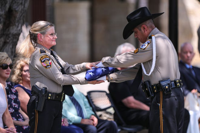 A folded flag is prepared for presentation to the family of Travis County sheriff's office Senior Deputy Christopher Korzilius at Austin Ridge Bible Church last week.
