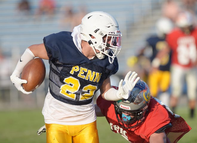 Moon's Dawson Snyder picks up some yards during the Penn-Ohio game Thursday night at Patterson Field in East Liverpool, Ohio.