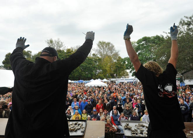 Contestants in the 2012 shuck-off competition at the Wellfleet OysterFest throw up their arms up after finishing their heat.  The 2021 event has been postponed due to pandemic concerns.