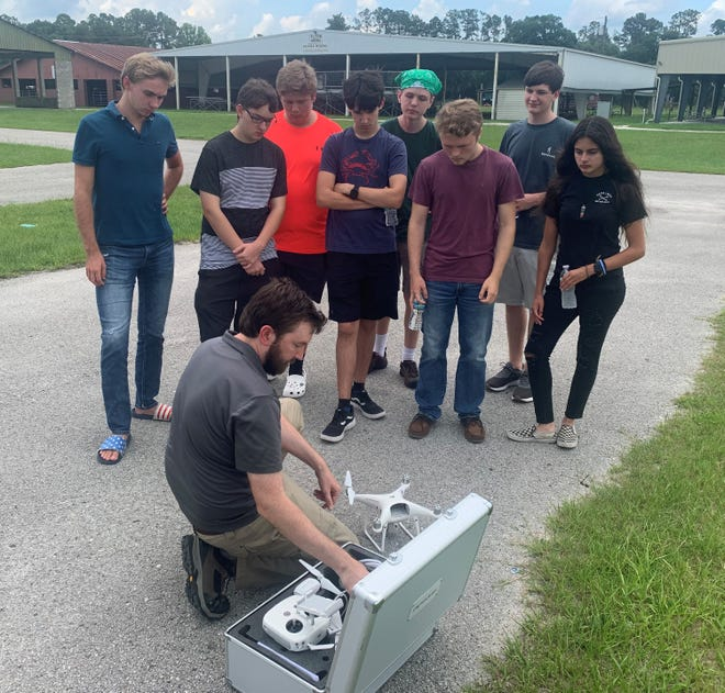 Camp participants learn about flying drones with Matt Smith, UF/IFAS Certified Drone Pilot. Pictured, left to right: John Williford, Jared Foley, Skyler Wahl, Mark Lewandowski, Samuel Weiner, Garrett Seyler, Brandon Stouffer and Paige Griner.