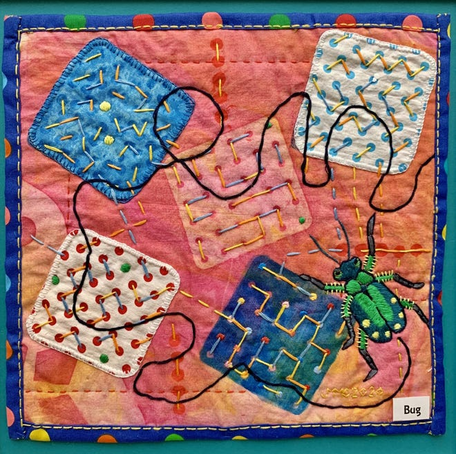 A vivid-colored piece of art designed by Mount Pleasant fabric artist Jean Caboth depicts a detailed and intricately embroidered bug and patterned squares.