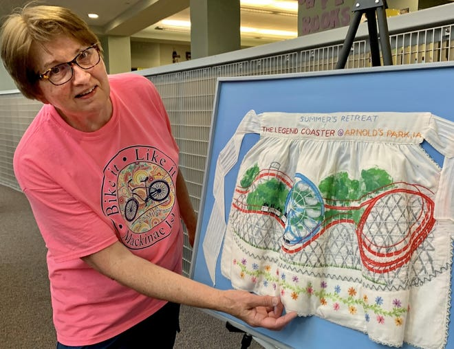 Fabric artist Jean Caboth of Mount Pleasant stands with an apron she embroidered with the Legend roller coaster at Arnolds Park. Built in 1927, the Legend is the seventh-oldest operating wooden coaster in the United States. An exhibit of Caboth's work is at Mount Pleasant Public Library through Labor Day.