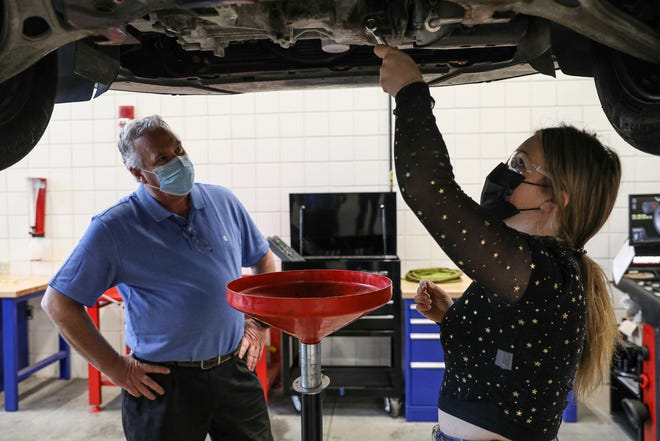 Dover High School teacher Eric Schlapak watches a student work in an automobile mechanics course. He has won a sabbatical to spend a year creating curriculum for applying math skills in career technical courses.