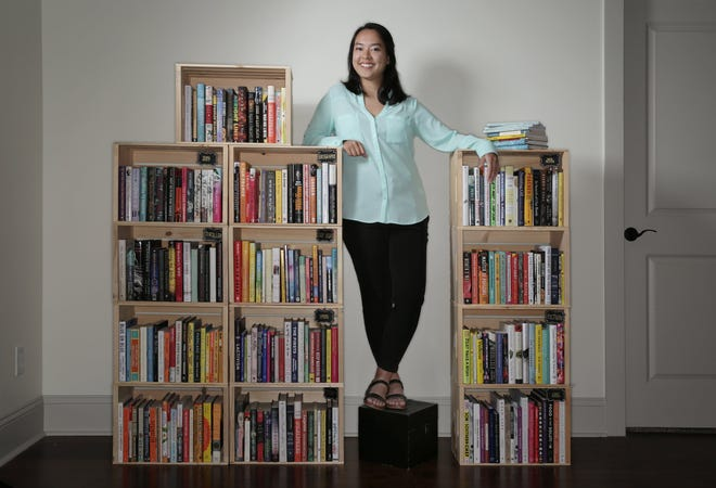 Vanessa Nicholle, owner of Femme Fire Books, a local pop-up bookstore that showcases books written by people of color and other marginalized identities, is photographed with some of the offerings at her Jacksonville home Thursday.