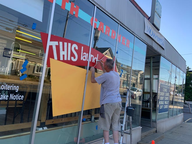 D.J. Bitters of Westminster paints a new sign on the window of the South Gardner Laundromat on June 24.