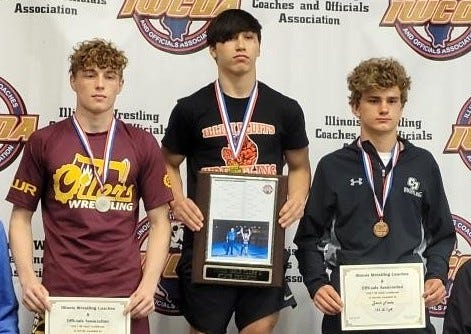 Illini Bluffs wrestler Paul Ishikawa stands atop the podium after winning a state championship at the Illinois Wrestling Coaches and Officials Association state finals Thursday in Springfield.