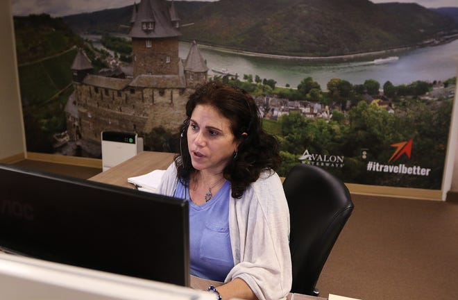 Rose Cacciatore, senior leisure travel consultant, helps a client while on duty at Travel Leaders Framingham, June 25, 2021. Behind her is a mural of the Rhine River flowing through Koblenz, Germany.