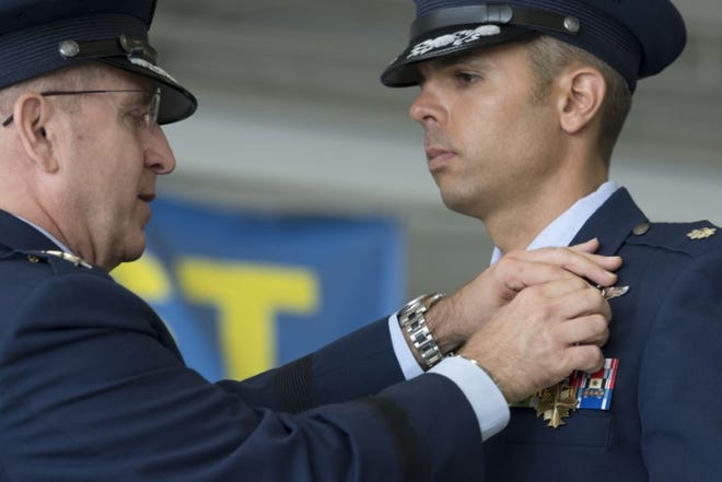 Lt. Col. Christopher McCall, 73rd Expeditionary Special Operations Squadron Shadow 71 aircraft commander, receives the Distinguished Flying Cross from Lt. Gen. Jim Slife, commander of Air Force Special Operations Command, during a Tuesday ceremony at Hurlburt Field. Shadow 71 was an AC-130J Ghostrider flight that supported American and Afghan forces in 2019 during an ambush and subsequent firefight.