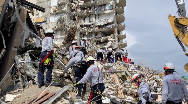 Search and rescue personnel search the rubble for survivors at the Champlain Towers South Condo in Surfside, Fla.