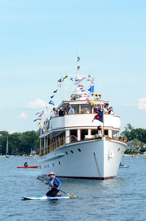 Paddleboards and kayaks glide past the flagship Canim in 2019 during the Harbor Springs Area Historical Society's annual Blessing of the Fleet boat parade. As watercraft passed the Canim, they received a blessing for a safe and enjoyable boating season.