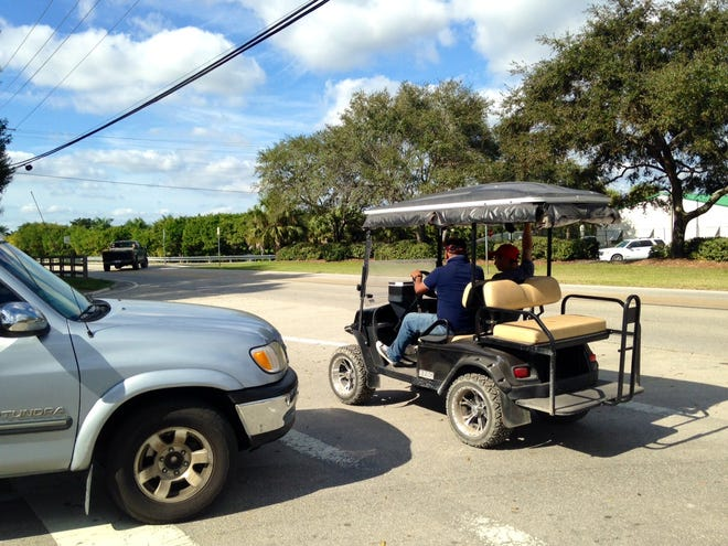 A golf cart  encounters traffic in Wellington in 2014. The village is considering establishing a minimum age of 15 to be permitted to drive a golf cart on Wellington's streets.