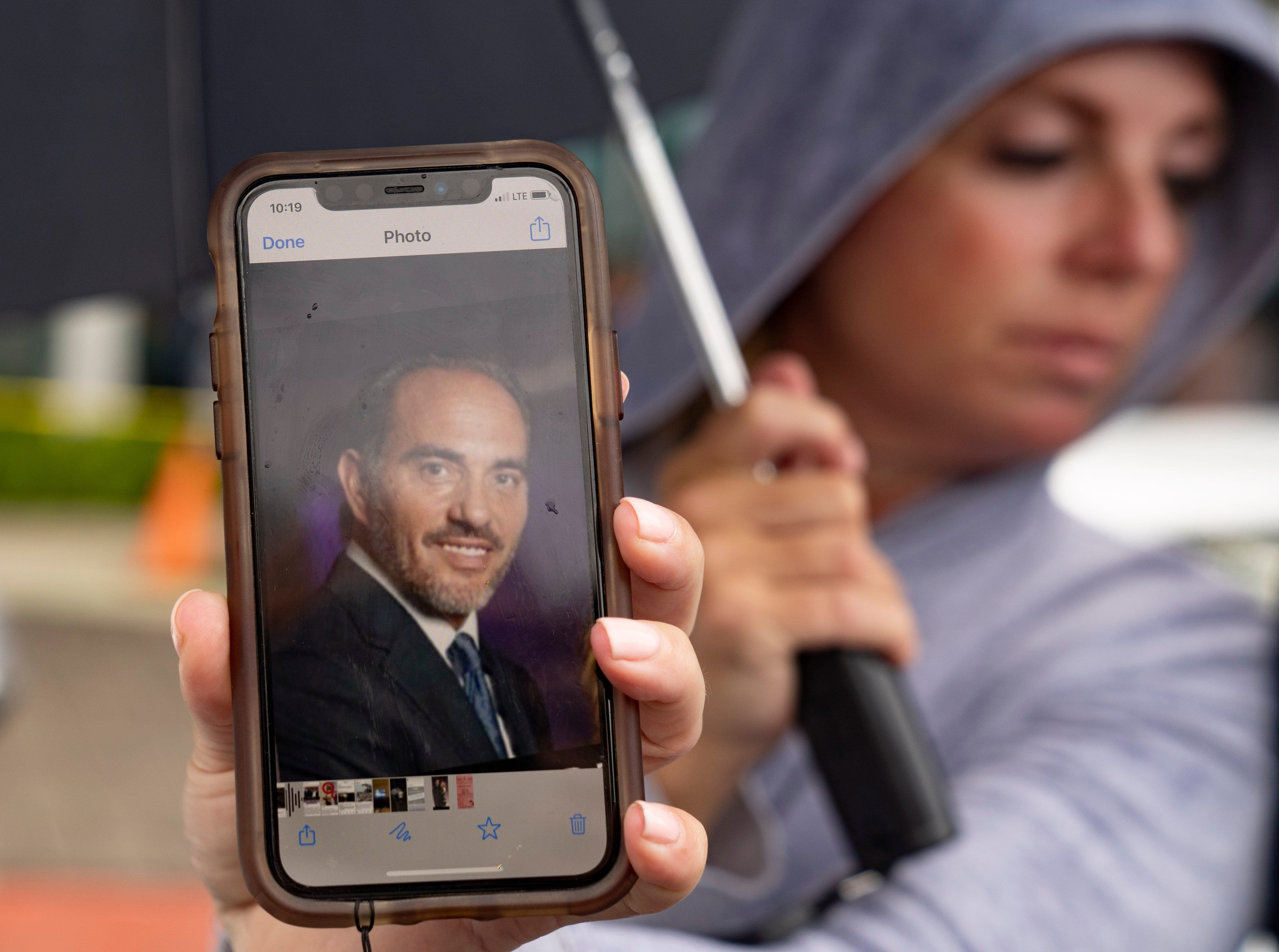 Toby Fried holds up a picture of her missing brother, Chaim Rosenberg (aka Harry Rosenberg), outside the Surfside Community Center on June 25, 2021 in Surfside, Florida. The 12-story Champlain Towers South condo building partially collapsed on Thursday. (Greg Lovett/The Palm Beach Post)