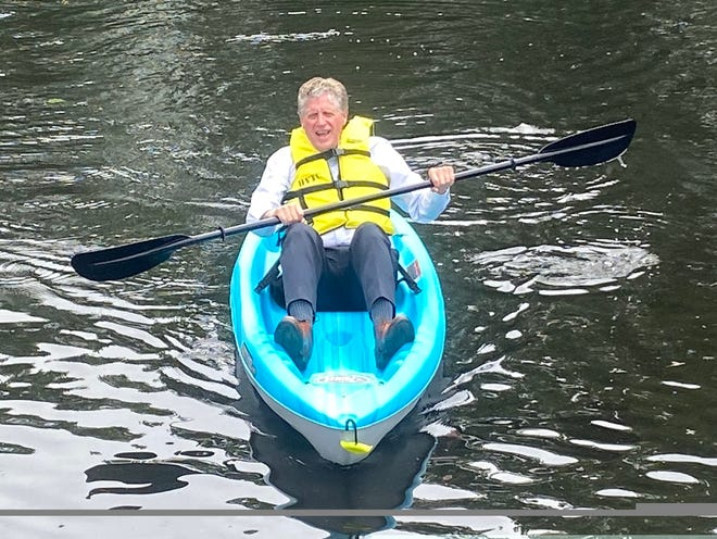 Gov. Dan McKee tries out one of the kayaks in Central Falls' new kayaking program, which aims to introduce at least 200 children to kayaking this summer.