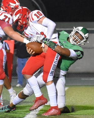 St. Mary's sophomore Jahzon Jacks (27) brings down Lodi quarterback Adam Schallberger in their game against the Flames Oct. 4, 2019, at St. Mary's High School.