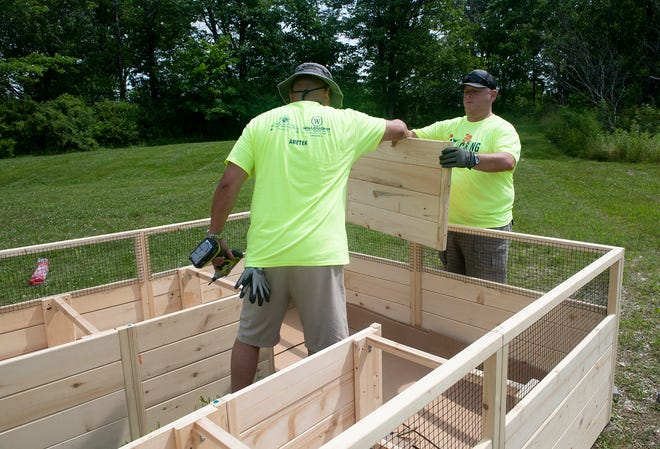 United Way's annual Day of Caring on Friday had volunteers working at nine sites in Portage County. Greg Bailey hands a board to Eric Schlaubach for a raised garden box at Children's Advantage.