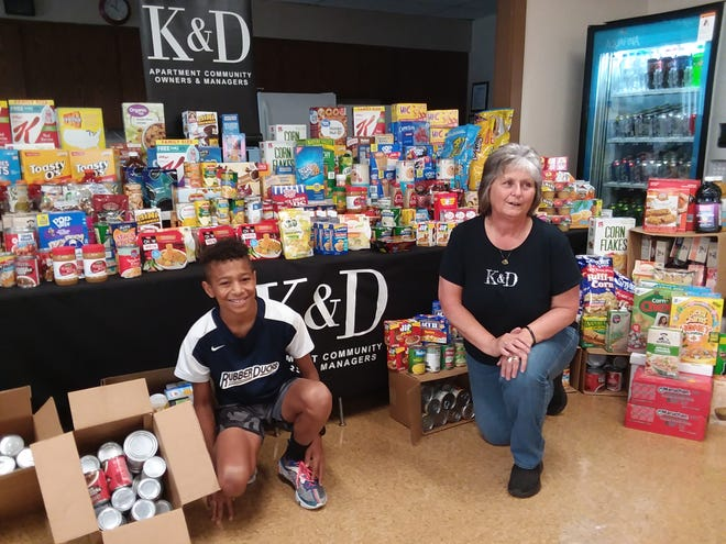 Logan Kuhn, 13, founder of Logan's Lunches, and Belden Towers property manager Joyce Karchner show some of the 920 pounds of food tenants donated on Friday to Logan's charity, which benefits the Stark County Hunger Task Force.