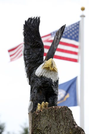 Falling leaves from a large maple tree became an eyesore for Jackson Township resident Terry Phillips. So he hired woodcarving artist Jack Riese, of Massillon, to transform the tree into a piece of art, consisting two eagles and a bear.