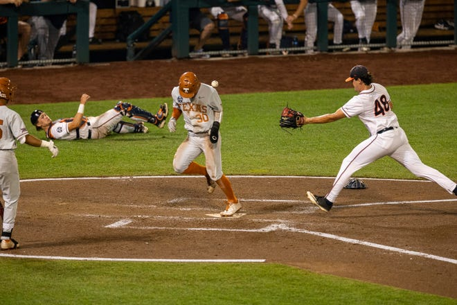Texas outfielder Eric Kennedy (30) runs home on a wild pitch by Virginia pitcher Mike Vasil (48) during a baseball game in the College World Series on Thursday at TD Ameritrade Park in Omaha, Neb.