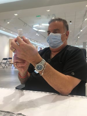 Walt Pannone fills a syringe with COVID-19 vaccine on the final day of the Sarasota Square Mall clinic.