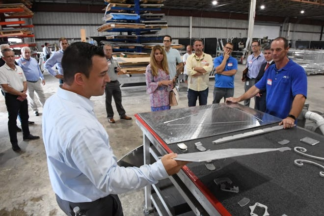 Neil Rainford, senior project executive for Mullet's Aluminum shows some products milled on a CNC machine to guests. Members of the Sarasota-Manatee Manufacturers Association toured Mullet's Aluminum Products manufacturing facility on McIntosh Rd. on Thursday.