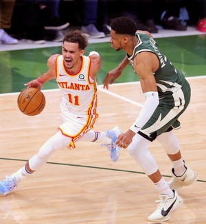 Atlanta Hawks guard Trae Young drives past Bucks defender Giannis Antetokounmpo during Game 1 of the NBA Eastern Conference finals game Wednesday, June 23, 2021, in Milwaukee.