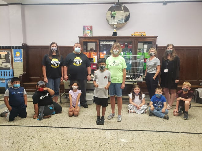 """Irving Summer School students presented a check for $357.50 to the Henry County Humane Society of Kewanee on Thursday. The fundraiser was part of the summer school's theme of """"Helping Hands in Our Community."""" The students, grades 2-3, came up with a fundraiser idea and raised money through a """"penny war."""" Teacher Melissa Newman's class collected the most money with $100. The top student fundraiser was Santi Montimyer, who donated the most money of $57 that he raised by doing extra chores. The students have spent the last several weeks learning about their community, and what it means to be a good citizen. Pictured, back row, from left, teacher Melissa Newman, 21st CCLC Site Coordinator Patick Peach, Irving Principal Tammy Brown and Counselor Tiffany Platz. Center, Santi Montimyer hands the donation over to HCHS Treasurer Mary Bergren."""