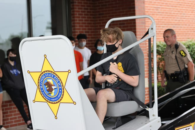 """Illinois State Trooper Jason Wilson, District #7 Safety Officer, spoke with the Kewanee High School Summer Driver Education Class June 24. Trooper Wilson brought with him the """"Convincer"""" crash simulator to help encourage students to wear their safety belts while driving. In the photo, KHS student Cooper Bates takes a ride on the Convincer."""