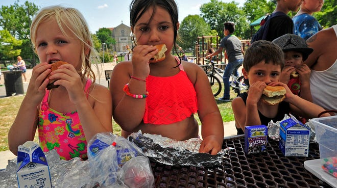 In this 2017 photo, Gennaligh Faith Souza, Hailey Furtado, Donnie and Brett Sylva enjoy the cheeseburgers during the New Bedford Parks, Recreation & Beaches Departments annual Play in the Park program at Brooklawn Park in New Bedford.