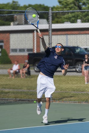 Connor Swartz serves during a doubles match with teammate Jason Demers.