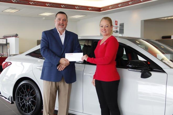 Bayhealth Foundation Director of Development Chuck Desch accepts a check for $10,000 from C.F. Schwartz Toyota Secretary/Treasurer Linda Schwartz-Chi.