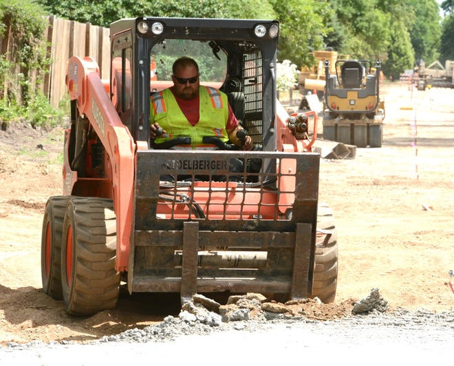 A construction worker on Thursday uses a forklift mounted on a skid steer loader to remove excess concrete from a paved section of 10th Avenue North. According to officials the project is on schedule.