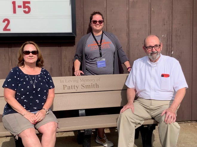 (L-R)Terry Glidden, Tabitha Johnson (standing) and Bob Smith check outthe new bench dedicated to Patty Smith at Tusky Branch Library.