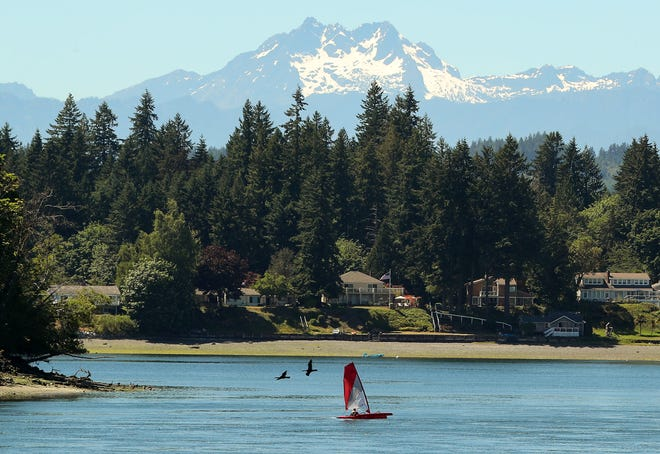 A small red sailboat cruises through the water off the shore of Pat Carey Vista in Bremerton on Friday, June 25, 2021.