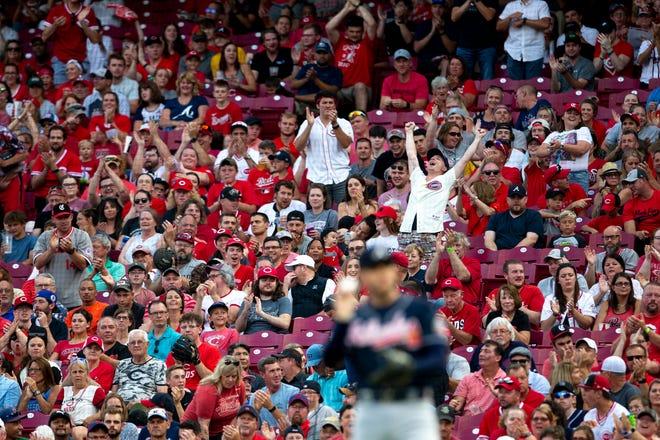 Cincinnati Reds fans cheer as the Cincinnati Reds take a 2-1 lead off a Cincinnati Reds first baseman Joey Votto (19) base hit in the third inning of the MLB baseball game between Cincinnati Reds and Atlanta Braves at Great American Ball Park in Cincinnati on Thursday, June 24, 2021.