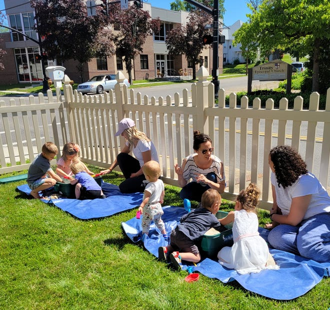Families participate in outdoor programming on the lawn of the Coshocton Public Library were fencing was recently installed to allow for outside activities.