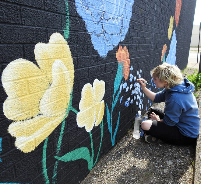 Coshocton High School senior Jaidyn Brink works on a selfie wall at Rust Décor on Sixth Street. A mural of a crow with a diamond in its beak will follow at Dean's Jewelry. Brink is hopeful of doing more artwork for businesses in the city.