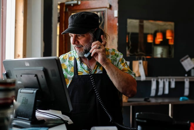 Greg Mudge owner of Mudgie's Deli and Bar in Detroit answers a phone call at the takeout order window of the restaurant, Thursday, June 24, 2021.