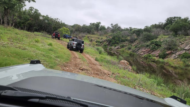 A line of Broncos at the Bronco Off-Roadeo rides along a stream. The scenery is ever-changing on the windy trails from water to rock to steep inclines.