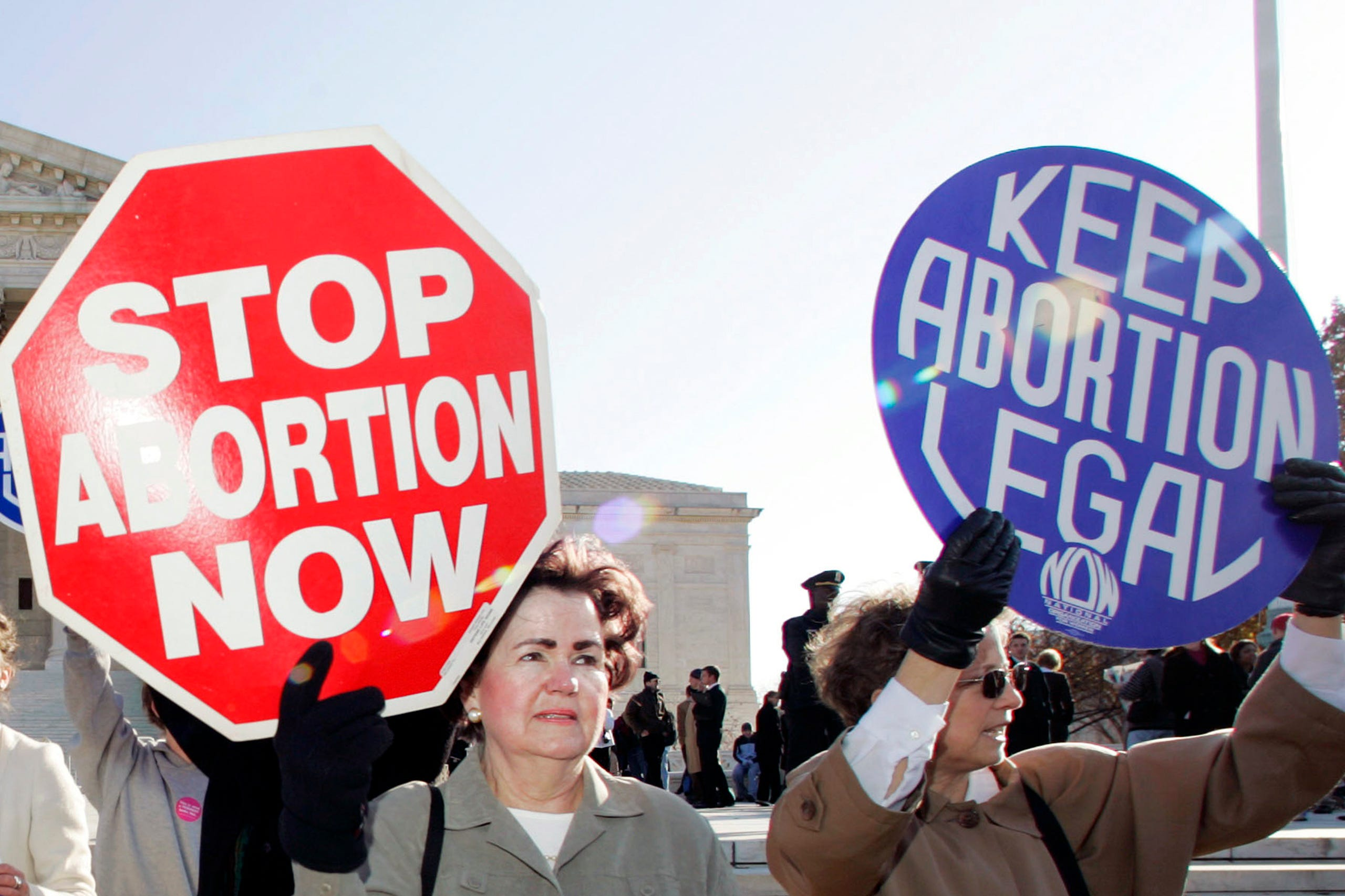 In this Nov. 30, 2005 file photo, an anti-abortion supporter stands next to a  pro-choice demonstrator outside the U.S. Supreme Court in Washington.