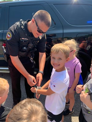Officer Riley Holloman shows Colton Morgan some of the equipment needed to do his job.