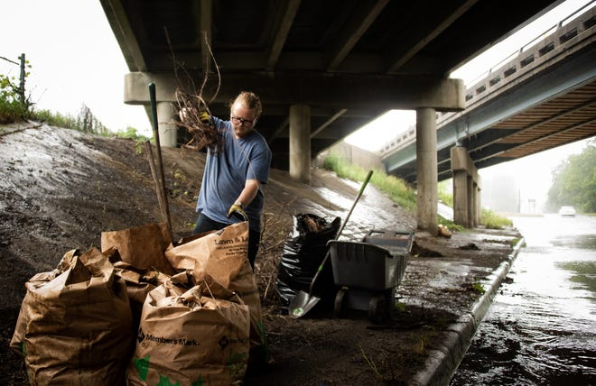 Despite heavy rain, east side resident Ryan Kost cleans up debris and overgrowth beneath I-496 on Holmes Street Friday, June 25, 2021.