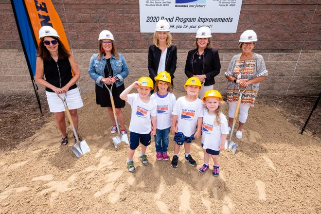 A group of kids pose for a photo with members of the East China Schools board at a groundbreaking ceremony Thursday, June 24, 2021, at the district's Performing Arts Center in East China.