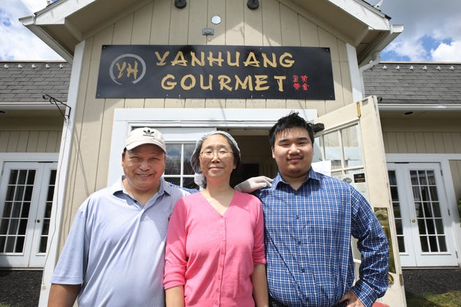 Yinquan Yan, left, wife Zhengxuan Huang, center, and son David Yan, 18, right, stand at the front door of their new authentic Chinese restaurant, Yanhuang Gourmet in Perinton, Wednesday, June 23, 2021.
