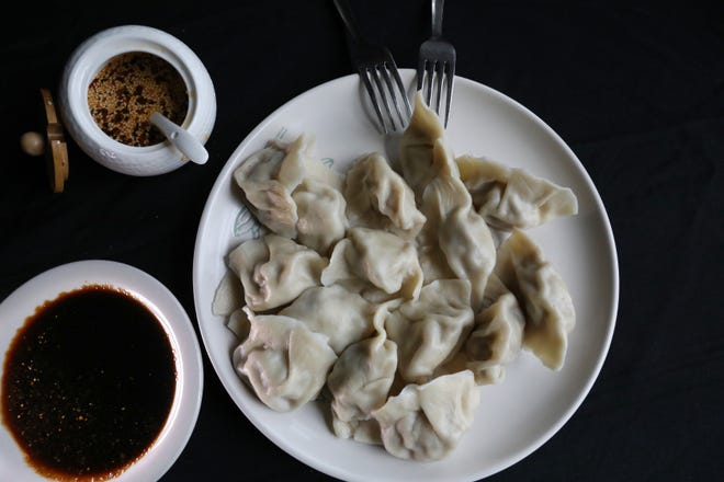 Pork and cabbage dumplings served with different dipping sauces at the new YANHUANG Gourmet in Fairport Wednesday, June 23, 2021.