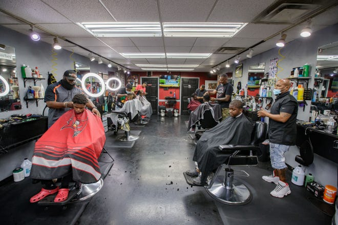 Customers get their hair done at Fade Barbershop while the barbers await the sentencing of Derek Chauvin Friday, June 25, 2021. A mental health training day for Black barbers, mentors is planned for July 11.